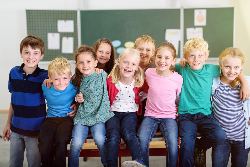 Cute Young Learners Inside their Classroom, Smiling at the Camera While Holding Each Other by Shoulder.
